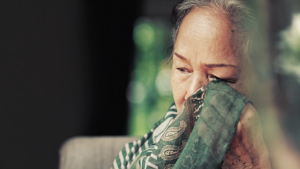 elderly woman wiping her eyes