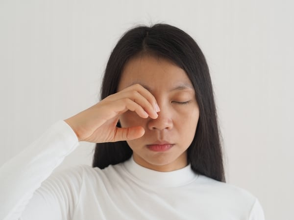woman rubbing her eyes